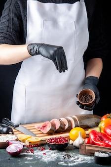 Vooraanzicht van chef-kok strooide zwarte peper op plakjes rauwe vis op snijplank groenten op houten serveerplank op keukentafel