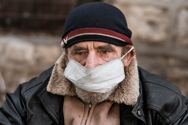 Vooraanzicht van dakloze man buitenshuis met medisch masker