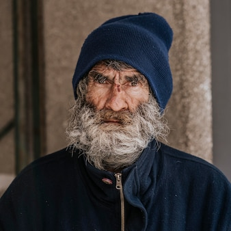 Vooraanzicht van dakloze man met een baard buitenshuis