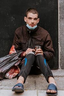 Vooraanzicht van dakloze man met medisch masker en beker