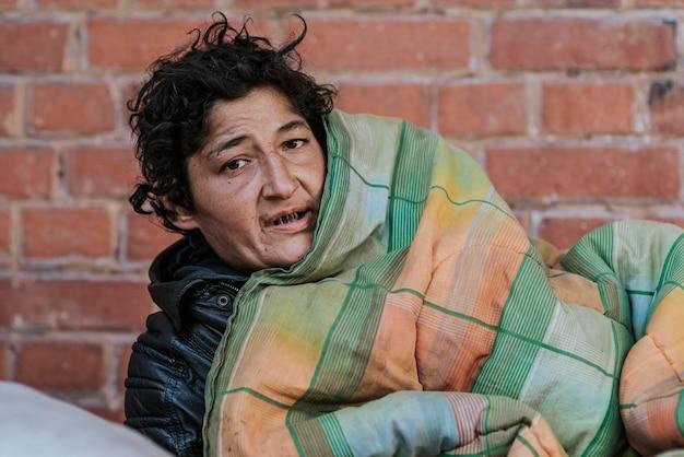 Vooraanzicht van dakloze vrouw onder deken buiten