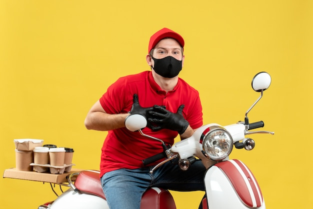 Vooraanzicht van dankbare koeriersmens die rode blouse en hoedenhandschoenen draagt in medisch masker die ordezitting op autoped levert