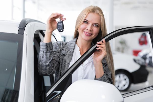 Vooraanzicht van de autosleutels van de vrouwenholding