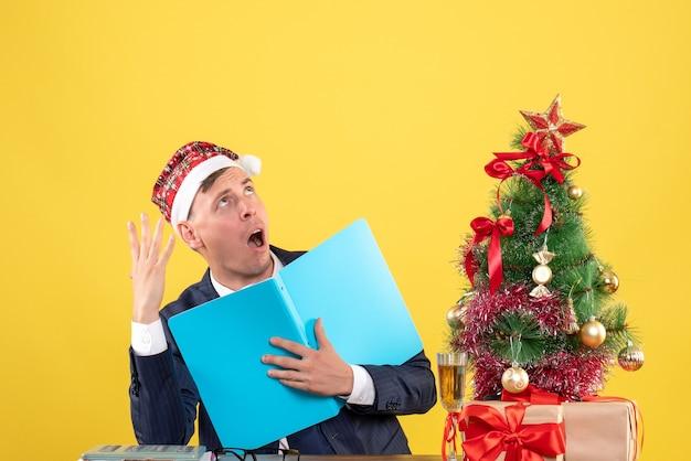 Vooraanzicht van de bedrijfsmens die documetns houdt die aan de lijst dichtbij kerstmisboom zitten en stelt op geel voor