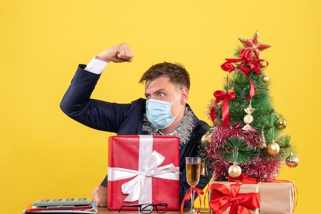 Vooraanzicht van de bedrijfsmens die kracht toont die aan de lijst in de buurt van de kerstboom zit en presenteert op geel.