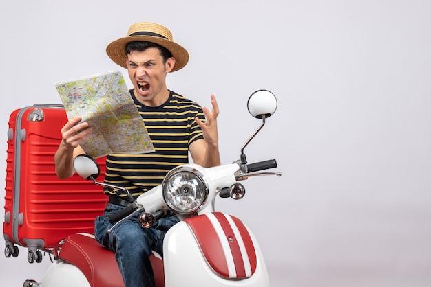 Vooraanzicht van de boze jonge man van de holdingskaart met strohoed op bromfiets
