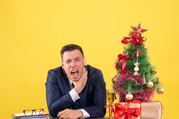 Vooraanzicht van de boze man die zichzelf met hand zittend aan de tafel wurgen in de buurt van kerstboom en geschenken op gele muur