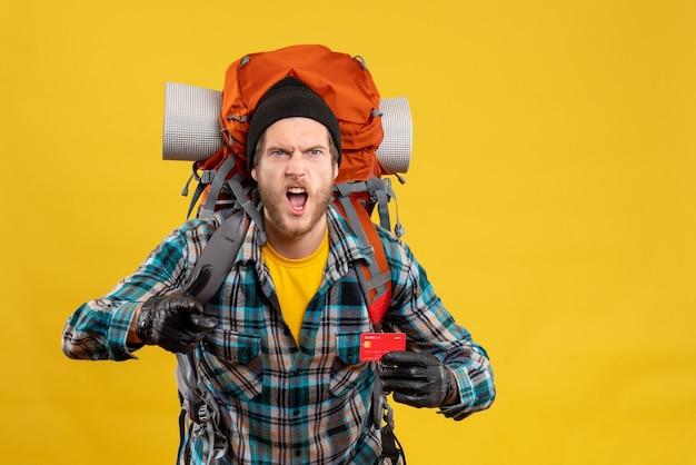 Vooraanzicht van de boze man met de creditcard van de backpackerholding naar voren wijzend
