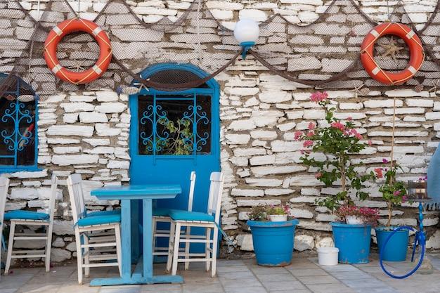 Vooraanzicht van de buitenkant van het strandcafé. tafel en lege stoelen buiten in de buurt van de stenen muur. toeristische plaatsen. typisch mediterraan restaurant, een vakantieplaats in de zomer. bodrum, turkije. detailopname