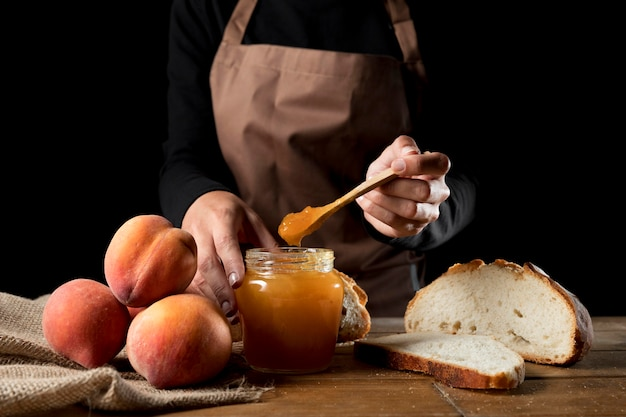 Vooraanzicht van de chef-kok met pot perzik marmelade