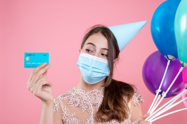 Vooraanzicht van de close-up schattig feest meisje met kroon en masker met ballonnen en kaart