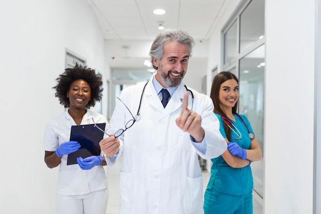 Vooraanzicht van de close-up van de groep van artsen en verpleegkundigen van gemengde leeftijd staan naast elkaar en kijken naar de camera.