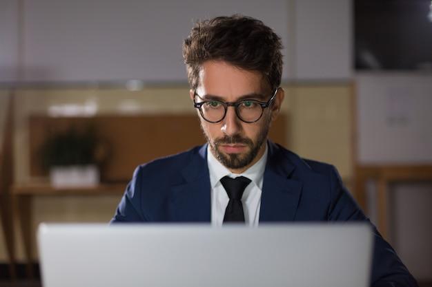 Vooraanzicht van de doordachte man in bril kijken naar laptop