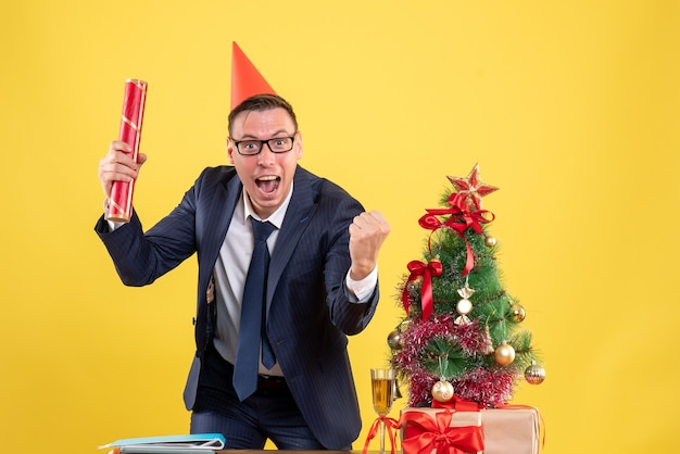 Vooraanzicht van de gelukkige bedrijfsmens die zich achter de lijst dichtbij de kerstboom bevindt en op geel stelt