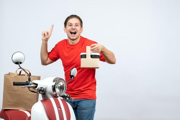 Vooraanzicht van de gelukkige bezorger in rode uniform staande in de buurt van scooter met volgorde die omhoog wijst op een witte achtergrond