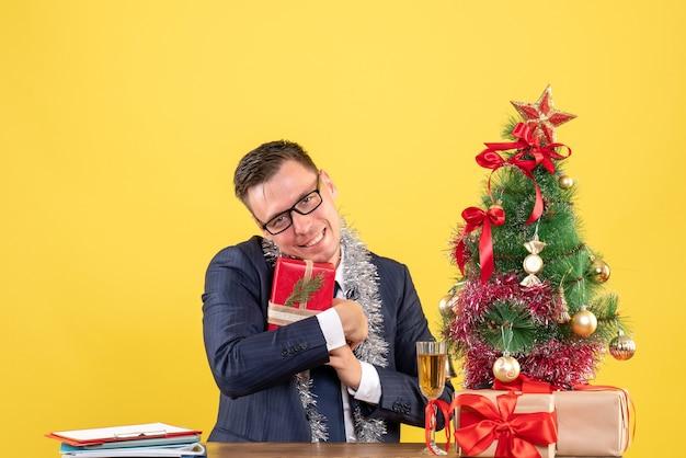 Vooraanzicht van de gelukkige man die zijn geschenk stevig vasthoudt aan de tafel in de buurt van de kerstboom en presenteert op geel