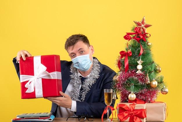 Vooraanzicht van de gift van de bedrijfsmensholding die aan de lijst in de buurt van de kerstboom zitten en presenteert op geel