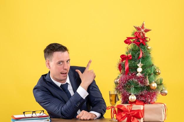 Vooraanzicht van de glimlachende mens die het teken van het vingerpistool maakt aan de lijst dichtbij kerstboom en giften op geel