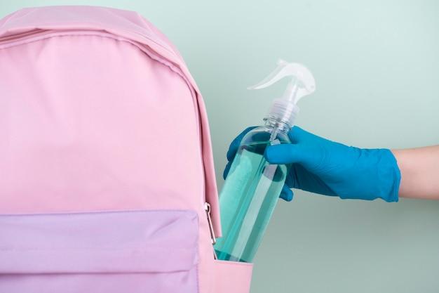 Vooraanzicht van de hand met chirurgische handschoen desinfecterende fles aanbrengend boekentas