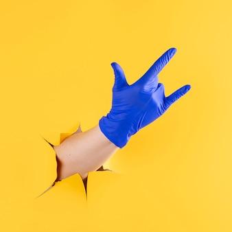 Vooraanzicht van de hand met chirurgische handschoen die rock and roll-gebaar toont