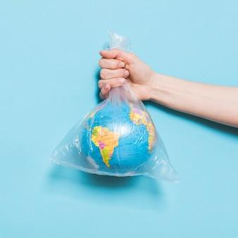 Vooraanzicht van de hand met wereldbol in plastic zak