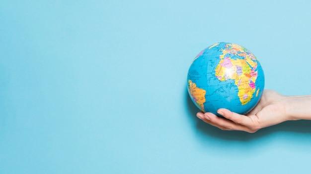 Vooraanzicht van de hand met wereldbol met kopie ruimte