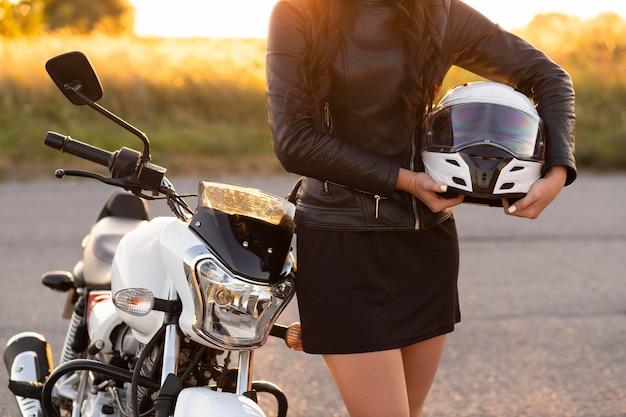 Vooraanzicht van de helm van de vrouwenholding en poseren naast haar motorfiets