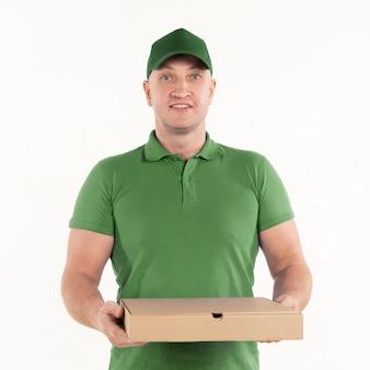 Vooraanzicht van de holdingspizza van de leveringsmens doos en het glimlachen