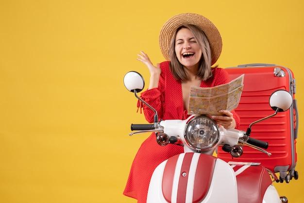 Vooraanzicht van de jonge dame in een rode jurk in de buurt van de kaart van de bromfiets