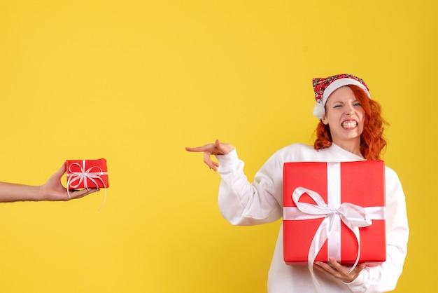 Vooraanzicht van de jonge kerstmis van de vrouwenholding op gele muur