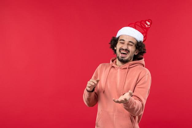 Vooraanzicht van de jonge man die gewoon lacht op de rode muur