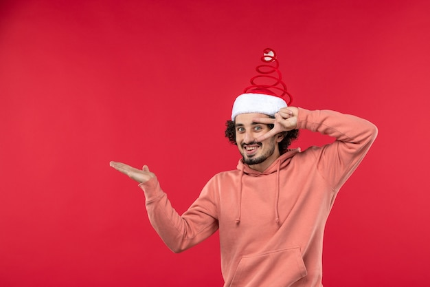 Vooraanzicht van de jonge man die lacht op de rode muur