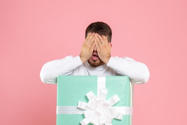 Vooraanzicht van de jonge man in de huidige doos die zijn gezicht op roze muur bedekt