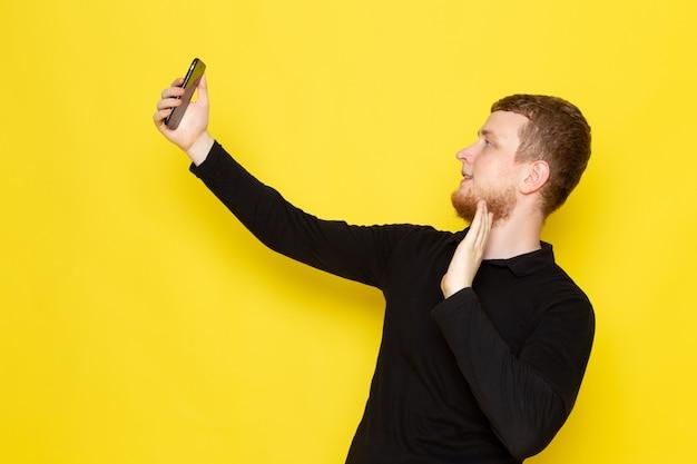 Vooraanzicht van de jonge man in zwart shirt nemen een selfie