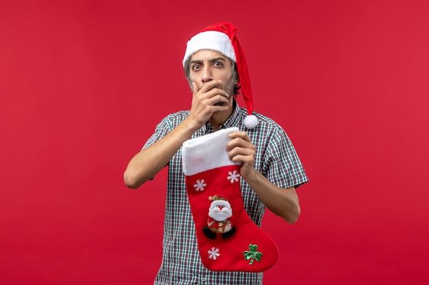 Vooraanzicht van de jonge man met kerstmissok op een lichtrode muur