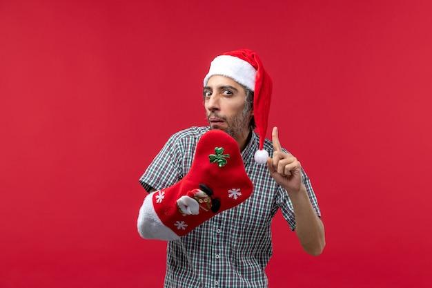 Vooraanzicht van de jonge man met kerstmissok op rode muur