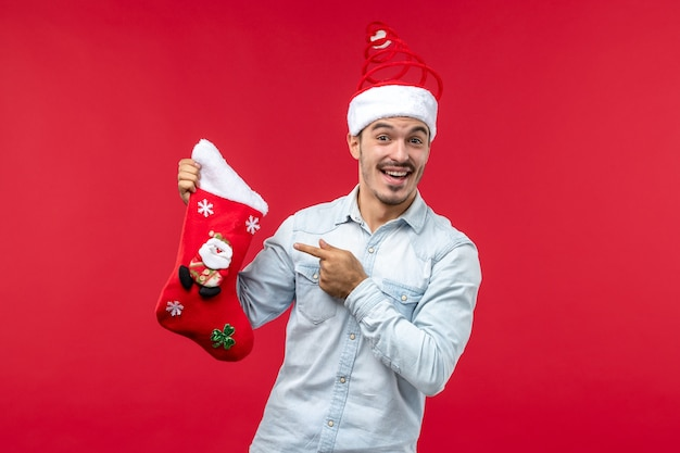 Vooraanzicht van de jonge man met rode kerstmissok op rode muur