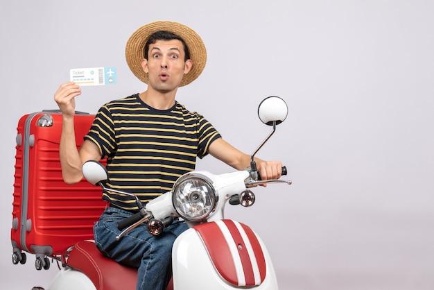 Vooraanzicht van de jonge man met strooien hoed op bromfiets met vliegticket