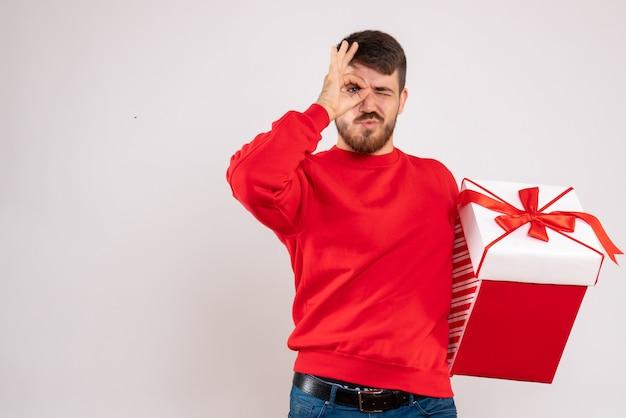 Vooraanzicht van de jonge mens die in rood overhemd kerstmis in doos op witte muur houdt