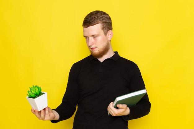 Vooraanzicht van de jonge mens die in zwart overhemd groene installatie en voorbeeldenboek houdt