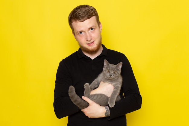Vooraanzicht van de jonge mens die in zwart overhemd leuk grijs katje op de gele oppervlakte houdt