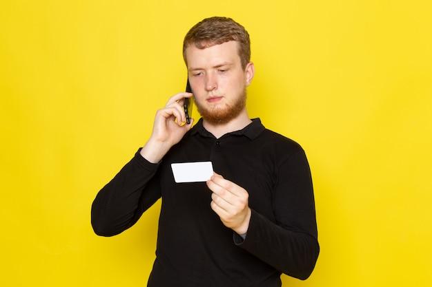 Vooraanzicht van de jonge mens die in zwart overhemd op de telefoon spreekt die witte kaart houdt