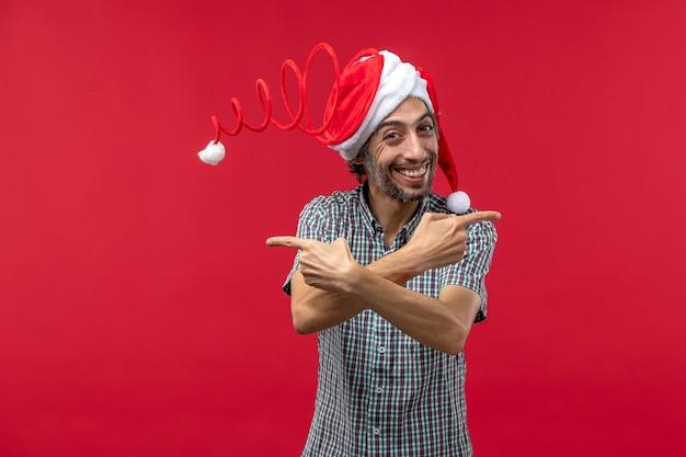 Vooraanzicht van de jonge mens die met grappig stuk speelgoed glb op rode muur glimlacht