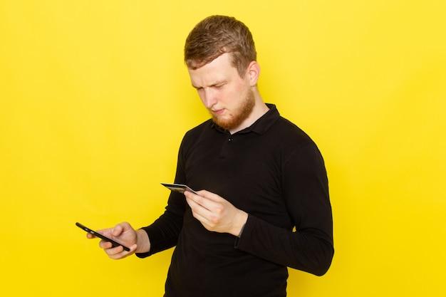 Vooraanzicht van de jonge mens in de zwarte kaart van de overhemdsholding en het gebruiken van een telefoon