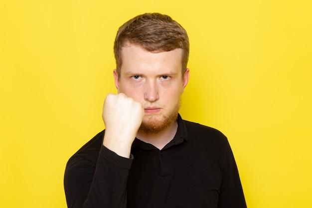 Vooraanzicht van de jonge mens in zwart overhemd die en met vuist stellen bedreigen