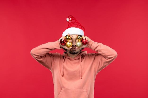 Vooraanzicht van de jonge mens met kerstboomspeelgoed op rode muur