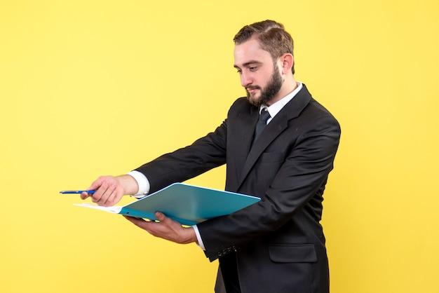 Vooraanzicht van de jonge mensenzakenman die pen opzij richt en de blauwe map op geel houdt