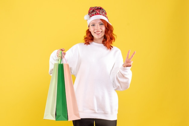 Vooraanzicht van de jonge pakketten van de vrouwenholding van winkelen op gele muur