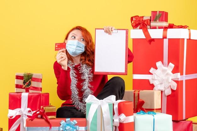 Vooraanzicht van de jonge vrouw die rond kerstmis zit presenteert in masker met bankkaart op gele muur