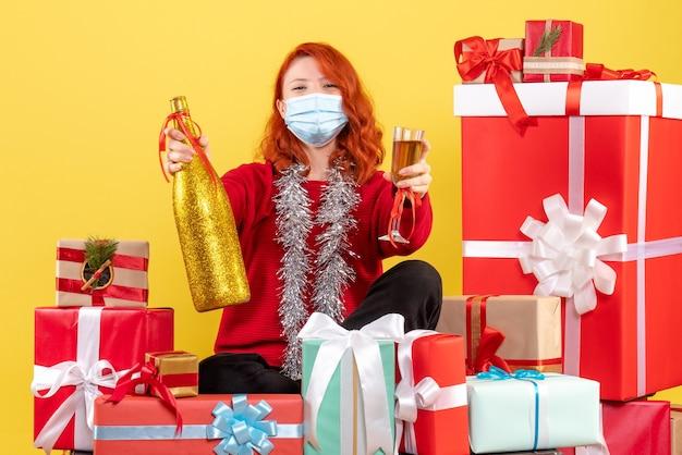 Vooraanzicht van de jonge vrouw die rond kerstmis zit presenteert in masker met champagne op gele muur